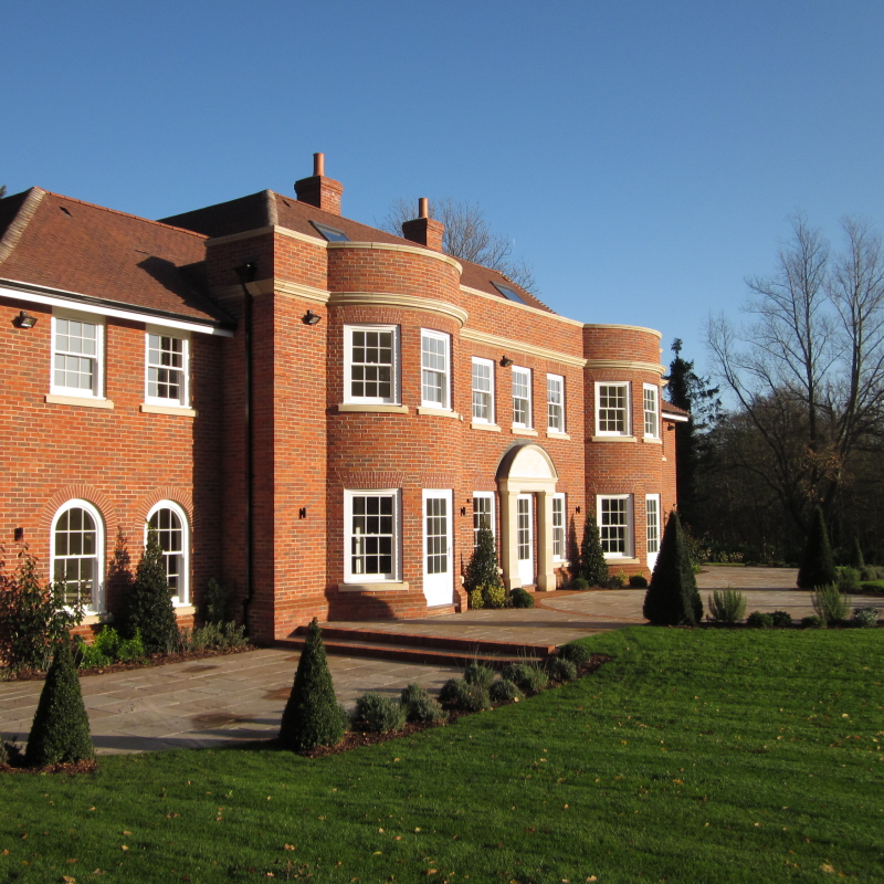 Red brick bespoke home, brick arches, stone front entrance